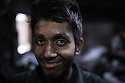 A young factory worker, covered in soot and grease, smiles for a picture in a metal bowl factory in Kamrangirchar, Dhaka, Bangladesh.