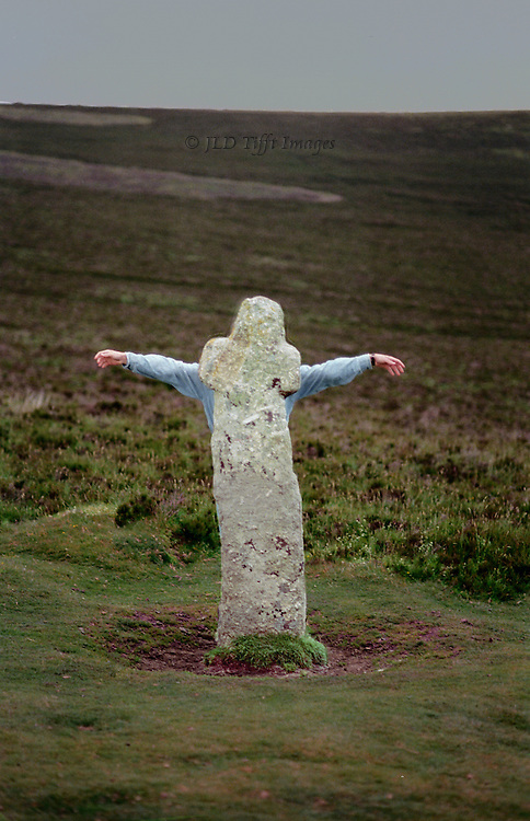 Standing stone on Dartmoor, faintly Christian cross shaped, made more so by the outstretched arms of a person standing behind it.