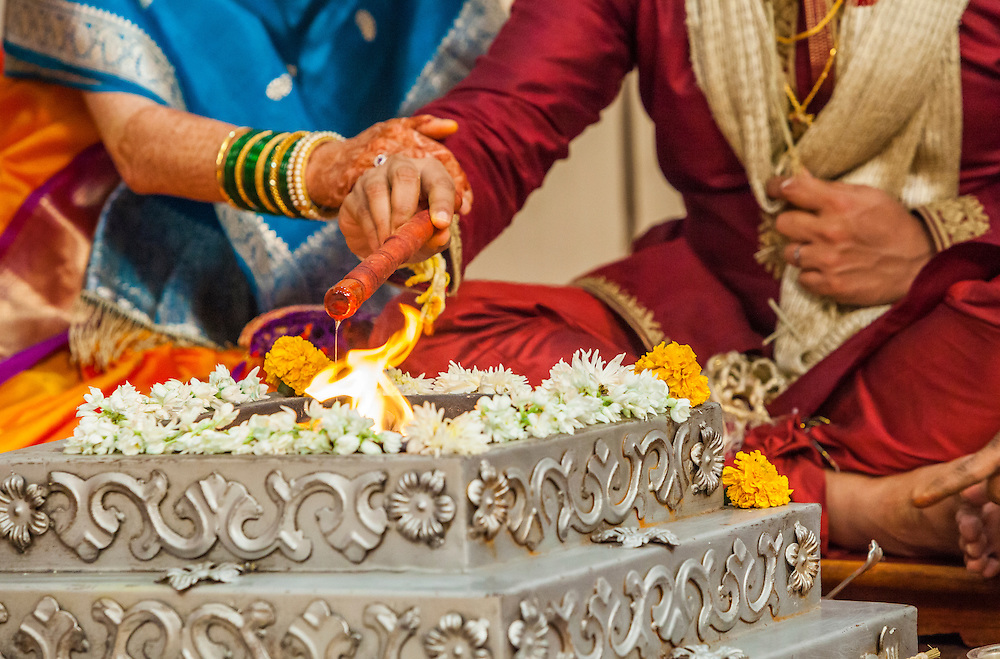 The bride and groom at a Indian wedding making offerings of oil to the holy fire.