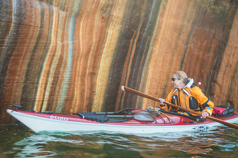 A kayaker paddles Lake Superior along the cliffs of Pictured Rocks National Lakeshore near Munising, Michigan which feature colorful stripes from dissolved minerals.