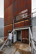 Tokyo, Japan, July 23 2016 - Outdoor pathway between the two towers of the Nakagin Capsule Tower, designed by architect Kisho Kurokawa and completed in 1972. The building is a rare example of Metabolism architecture movement.