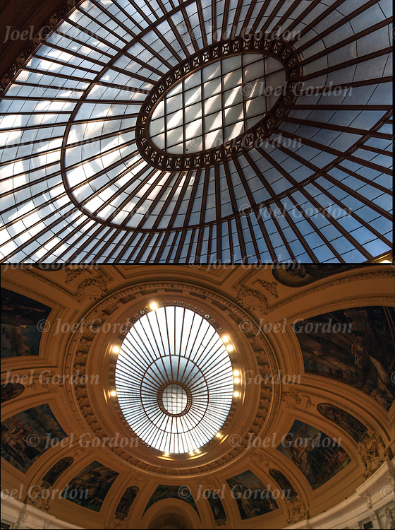 Two imaes of the rotunda looking up.<br /> <br /> The Rotunda, in the Alexander Hamilton U.S. Custom House, which is oval in shape and is one hundred and thirty-five feet long, eighty-five feet wide, and forty-eight feet high. The ceiling of the rotunda is a dome. It is one of the tile-and-plaster, vaulted masterpieces of the Spanish engineer Guastovino. It weighs one hundred and forty tons and contains no steel. In the center of the dome is an oval ceiling sash surround by painted murals with a skylight above<br /> <br /> The rotunda of the custom house is flanked on three sides by the museum's main exhibition galleries.