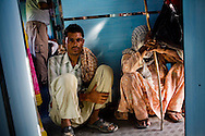 Village folk squat by the door as they ride the train for free from Dhuri Junction Stn. to Sangrur Stn., Punjab on 7th July 2009.. .6318 / Himsagar Express, India's longest single train journey, spanning 3720 kms, going from the mountains (Hima) to the seas (Sagar), from Jammu and Kashmir state of the Indian Himalayas to Kanyakumari, which is the southern most tip of India...Photo by Suzanne Lee / for The National
