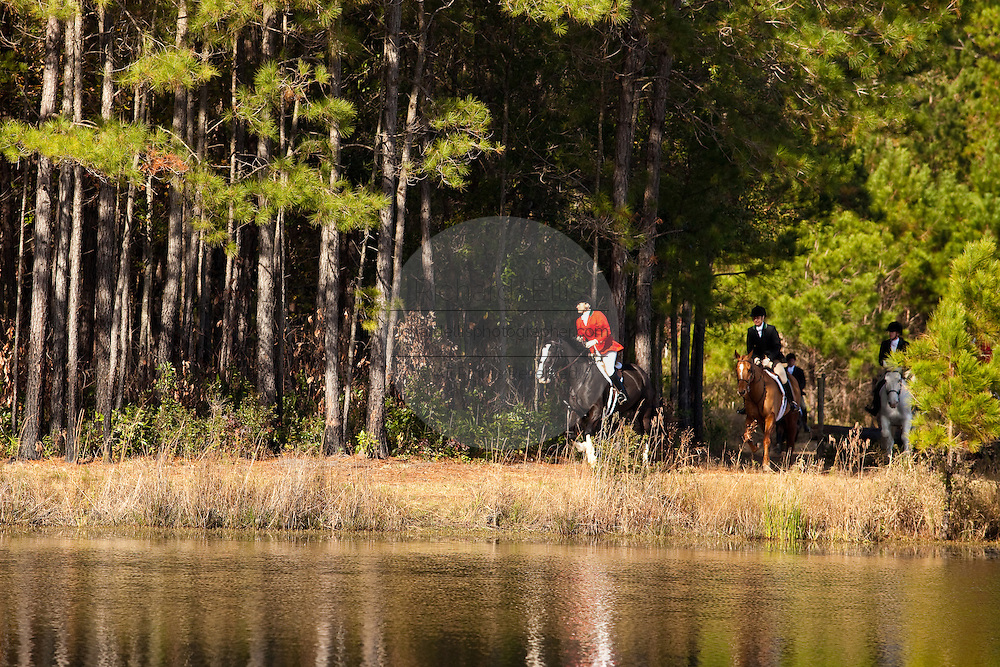 Fox hunters chase the scent along a lake during the Middleton Place foxhunt at Middleton Place plantation in Charleston, South Carolina. The hunt is a drag hunt where a scented cloth is used instead of live fox.