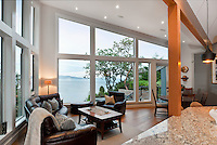 An extensive renovation on an ocean-side home in Ten Mile Point enhances the view over the water with a prow-like set of large windows, kitchen island with a sink looking toward the view, and warm woodwork.
