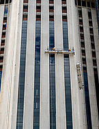 New Orleans, Louisiana, USA -- May 27, 2019. Men are on a scaffold high in the air working to refurbish a skyscraper in downtown New Orleans, LA.