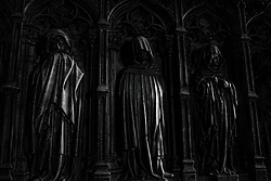 Three dark figures adorning the walls of Santa Eulalia Cathedral, Barcelona.