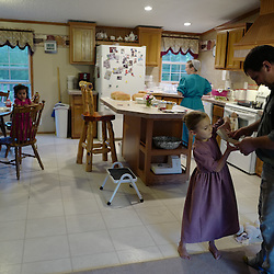 Martin Kauffman along with his six year-old daughter Staci looks through a box of pictures as fifteen month-old Holly stands on a chair as his wife Kathy prepares dinner at their home in Leasburg, Missouri on Tuesday, Sept. 27, 2016. (Photo by Keith Birmingham Photography)