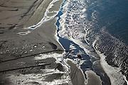 Nederland, Zuid-Holland, 's-Gravenzande, 18-03-2009; Versterking van de kust van Delfland tussen Slag Beukel en Slag Vluchtenburg, starnd en branding met tegenlcht. In de voorgrond de zandpersleidingen waarmee zand op het strand gespoten is, een shovel verplaatst buizen. De kust tussen Hoek van Holland en Den Haag is een van de 'Zwakke Schakels' in de zeewering. .Strengthening of the coast of Delfland between Hoek van Holland and The Hague by means of sand-supplementation. Pipes for transport of sand in the foreground are transported by a shovel. Beach and breakers with backlight..Swart collectie, luchtfoto (toeslag); Swart Collection, aerial photo (additional fee required); .foto Siebe Swart / photo Siebe Swart