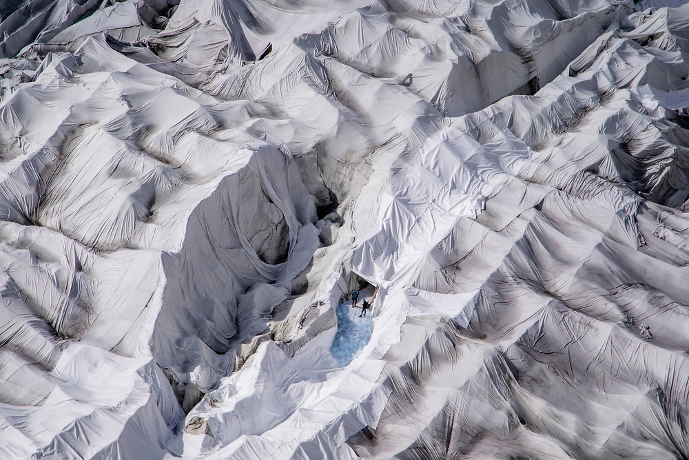 Two persons can be seen at the entrance of the glacier ice cave owned and maintained by the Carlen family. The ice cave at the mouth of the Rhone Glacier is covered every year with huge sheets of fleece blankets. to slow down the inevitable melting of the glacier due to warmer climate.