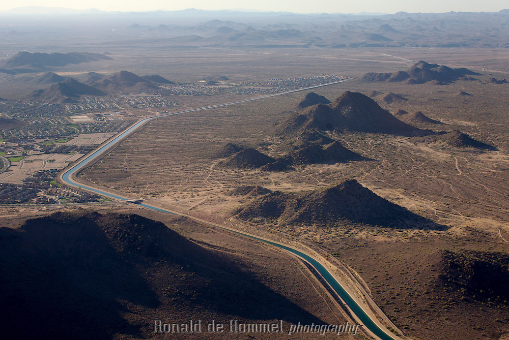 The Central Arizona Project (CAP), near Phoenix is a 500 mile long water canal that supplies Phoenix and Tucson with more than 70% of their water needs. The canal takes its water from the Colorado River. ..Phoenix Arizona. This city of 1,5 million inhabitants is located in the northeastern reaches of the Sonoran Desert. It has the hottest climate of any major city in the United States. The average high temperatures are over 100°F (37.8°C) for three months out of the year, and have spiked over 120°F (48.9°C) on occasion. Phoenix and it's surroundings are home to more that 200 bright green golf courses surrounded by yellow and red desert.