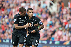 STOKE-ON-TRENT, ENGLAND - Sunday, August 9, 2015: Liverpool's Philippe Coutinho Correia celebrates scoring the first goal against Stoke City with team-mate James Milner during the Premier League match at the Britannia Stadium. (Pic by David Rawcliffe/Propaganda)