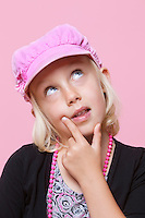 Thoughtful young girl wearing cap with finger on chin over pink background