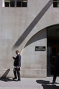 Businessman walks under diagonal shadow on a wall, off Fleet Street in the City of London.