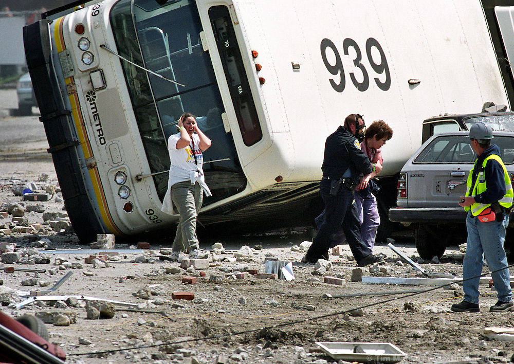 A Seattle police officer helps victims of a mock terrorist attack south of downtown on Monday, May 12, 2003 in Seattle, Washington. Controllers set off an explosion shortly after noon which simulated the detonation of a radioactive dispersal device or 'dirty bomb.'