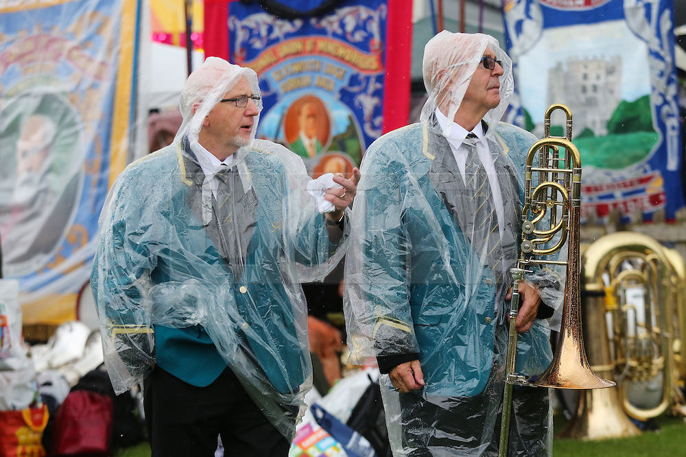 © Licensed to London News Pictures. 09/07/2016. Durham, UK. Band members wear plastic ponchos to protect themselves from the rain at the Durham Miners' Gala in County Durham, UK. The gala is a large gathering held annually associated with the coal mining heritage and trade unionism. Photo credit : Ian Hinchliffe/LNP