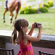 Child shutter-bug photographer at a horse show.<br />