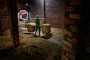 A worker carries a 50kg loads of rice husks to a storage room in one of Sa Dec's brick factories. The husks will be used to fuel kilns that will harden up to 150 000 bricks at a time. The brick factories of Sa Dec pump clay and water from the Mekong river, which they form into molds before firing them in kilns fueled by rice husks grown from river water.