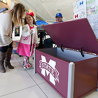 Thomas Wells | BUY AT PHOTOS.DJOURNAL.COM<br /> Being an Ole fan Avery Kate McCain looks to her mom about dropping their raffle ticket into a Mississippi State University toy box built by Herb Wall to raise money for the Tupelo High School to attend the inauguration of Pres. elect Donald Trump.
