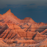 Warm light at sunset accentuates the the colors of the layers in Badlands National Park South Dakota.