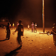 I began photographing life at night in African cities and towns eight years ago. Originally, I stepped into the streets at with my camera because I was intrigued by the buzz in communities after sunset. I was drawn to the way the patchy and bare streetlights brushed and defined the people and their activity. As a photojournalist, I am often assigned to report on the tragic or the exotic stories that dominate the news from Africa. In African Nights, however, I explore more universal themes like work, family, and community. My intention is to make images that are spontaneous. I walk the streets with a single camera and a fixed lens. I do not use a tripod or flash. Because of the low shutter speeds and differences in light sources, I often cannot predict what I will achieve. It is this mixture of brief encounters and unpredictability that continues to inspire this work. <br /> <br /> This project is a traveling exhibition with 18 framed photographs, 20&quot; X 24&quot; in two crates.