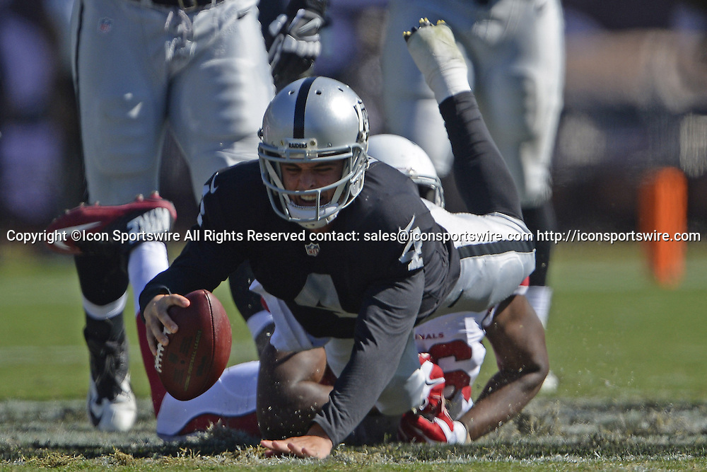 Oct. 19, 2014 - Oakland, CA, USA - Oakland Raiders quarterback Derek Carr (4) gets tripped up by Arizona Cardinals defensive end Kareem Martin (96) while running with the ball during the second quarter on Sunday, Oct. 19, 2014, at O.co Coliseum in Oakland, Calif