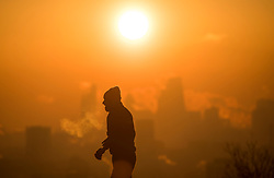 © Licensed to London News Pictures. 12/12/2017. London, UK. A walker watches the sun rise over the city of London from Hampstead Heath in north London on a freezing morning. Temperatures across the the UK dipped overnight with some regions expected to drop to -13C (9F). Photo credit: Ben Cawthra/LNP