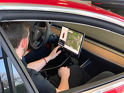 """MANCHESTER, ENGLAND - Monday, December 17, 2018: A sales person shows off the features of the 15"""" touch screen inside the new Tesla Model 3 car on display in red at the Manchester Tesla showroom, one of only two Model 3 cars in the UK, ahead of its European launch. (Pic by David Rawcliffe/Propaganda)"""