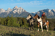 A wrangler and his horses pause to survey the sage flats in Jackson Hole, WY with the majestic Grand Teton mountain range projecting from the valley floor behind them.