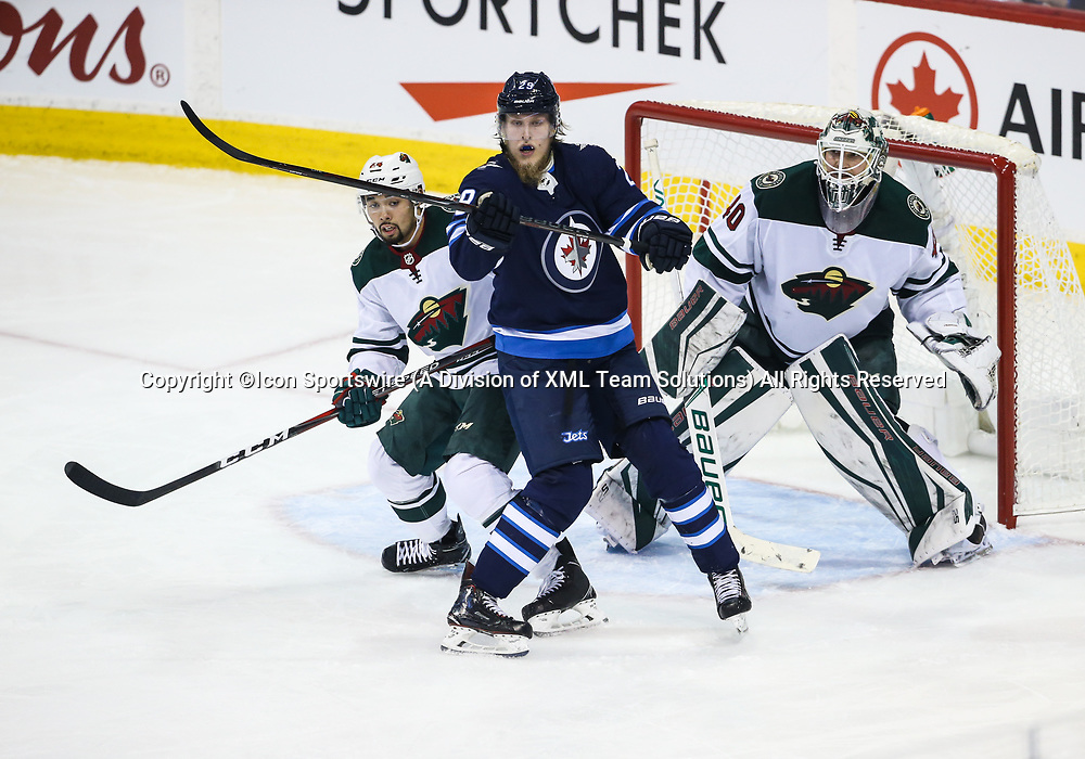 WINNIPEG, MB – April 11: Winnipeg Jets forward Patrik Laine (29) jostles for position with Minnesota Wild defenseman Matt Dumba (24) in front of Minnesota Wild goalie Devan Dubnyk (40) during the Stanley Cup Playoffs First Round Game 1 between the Winnipeg Jets and the Minnesota Wild on April 11, 2018 at the Bell MTS Place in Winnipeg MB. (Photo by Terrence Lee/Icon Sportswire)
