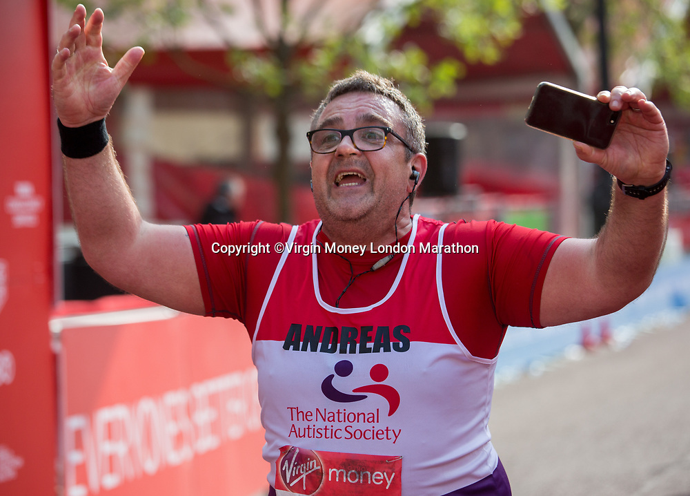 A runner crosses the line at the end of their 26.2 miles on The Mall. The Virgin Money London Marathon, 23rd April 2017.<br /> <br /> Photo: Roger Allen for Virgin Money London Marathon<br /> <br /> For further information: media@londonmarathonevents.co.uk