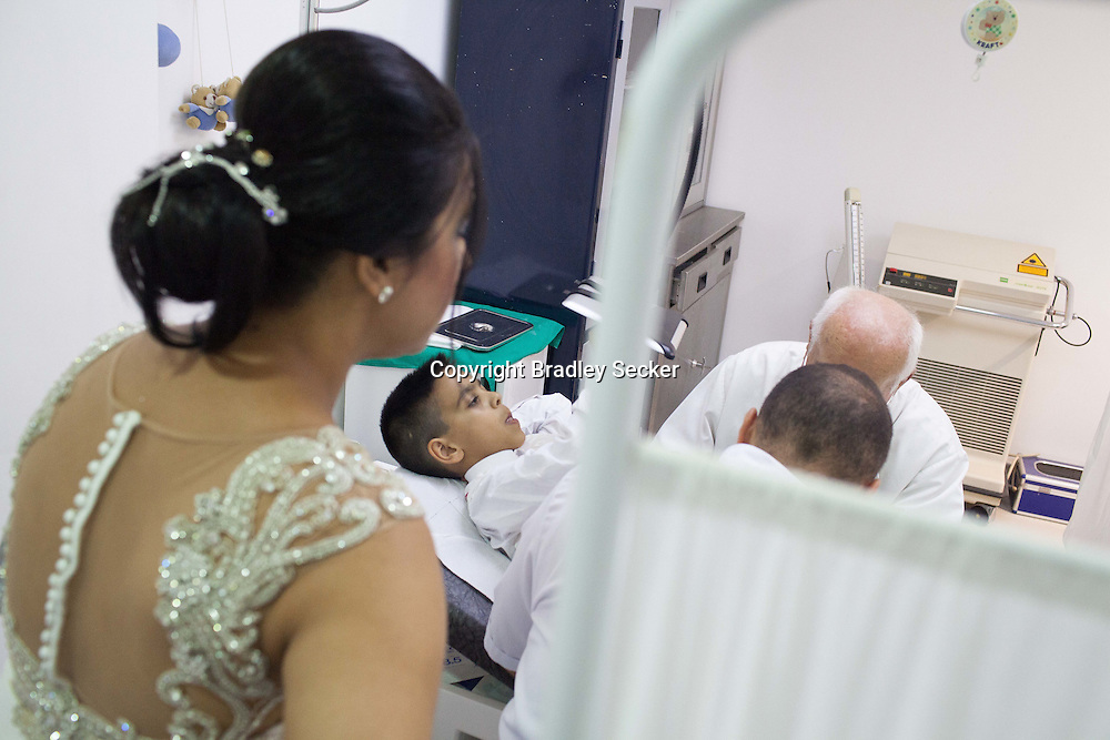 A patient uses an iPad as a distraction whilst he is being checked over by Dr Levent Ozken before leaving the circumcision palace for his coming of age 'Sünnet' day. Istanbul, Turkey.