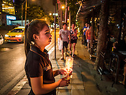 12 AUGUST 2015 - BANGKOK, THAILAND: A waitress at a restaurant in Bangkok holds a candle to honor Queen Sirikit of Thailand on the Queen's 83rd birthday. Queen Sirikit was born Mom Rajawongse Sirikit Kitiyakara on August 12, 1932. She is the queen consort of Bhumibol Adulyadej, King (Rama IX) of Thailand. She met Bhumibol in Paris, where her father was the Thai ambassador. They married in 1950, she was appointed Queen Regent in 1956. The King and Queen had one son and three daughters. She has not made any public appearances since her hospitalization in 2012. Her birthday is celebrated as Mother's Day in Thailand, schools and temples across Thailand hold ceremonies to honor the Queen and mothers.     PHOTO BY JACK KURTZ