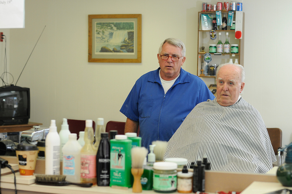 Barbers Mark Cooper and E.G. Estep at the Gardiner Lane Shopping Center Barber Shop Thursday, July 10, 2008 in Louisville, Ky. Cooper, at the left chair, cuts Charlie Corrigan's hair while E.G. Estep works on Ron Bisig,both longtime customers. (Photo by Brian Bohannon/www.brianbohannon.com)
