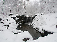 Snow storm at the waterfall in the North Woods in Central Park