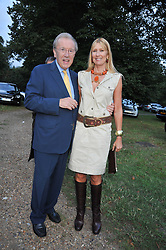 SIR DAVID & LADY CARINA FROST at a Summer party hosted by Lady Annabel Goldsmith at her home Ormeley Lodge, Ham, Surrey on 14th July 2009.