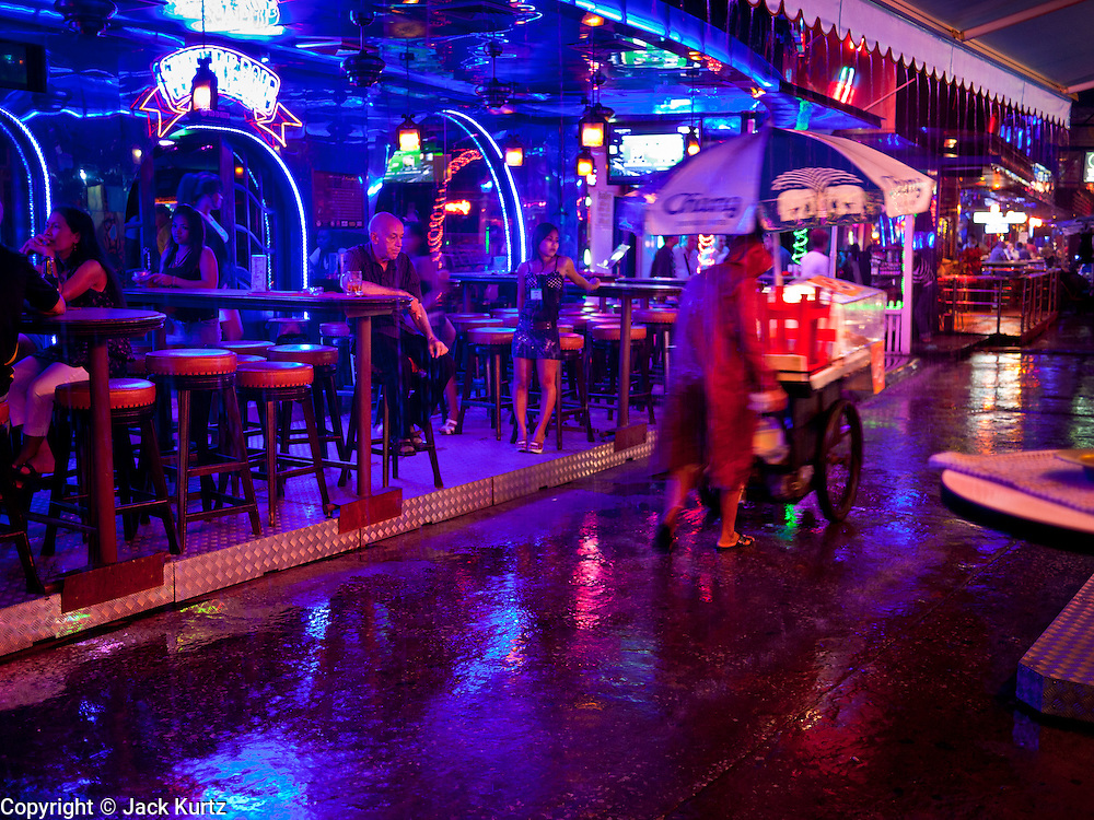 """12 JULY 2011 - BANGKOK, THAILAND: A noodle vendor pushes his cart past a beer bar frequented by prostitutes and their customers on Soi Cowboy, a """"red light"""" district in Bangkok during a rainy season downpour.  Prostitution in Thailand is illegal, although in practice it is tolerated and partly regulated. Prostitution is practiced openly throughout the country. The number of prostitutes is difficult to determine, estimates vary widely. Since the Vietnam War, Thailand has gained international notoriety among travelers from many countries as a sex tourism destination. One estimate published in 2003 placed the trade at US$ 4.3 billion per year or about three percent of the Thai economy. It has been suggested that at least 10% of tourist dollars may be spent on the sex trade. According to a 2001 report by the World Health Organisation: """"There are between 150,000 and 200,000 sex workers (in Thailand).""""  PHOTO BY JACK KURTZ"""