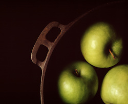 FOOD Three green cooking apples in cast iron pot.