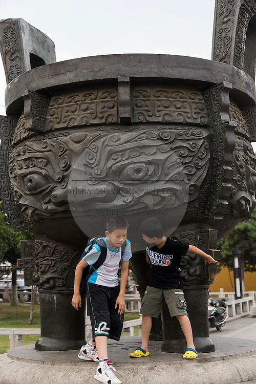 Children play around a giant brass urn on Tiger Hill in Suzhou, China.