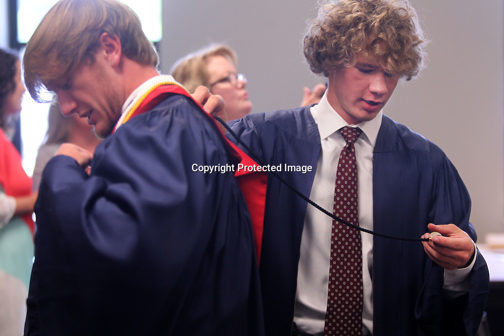 Adam Robison | BUT AT PHOTOS.DJOURNAL.COM<br /> TCPS graduating senior Robert Stevens, right, helps classmate Drew Hurst get ready for their graduation ceremony at the Orchard Saturday in Tupleo.
