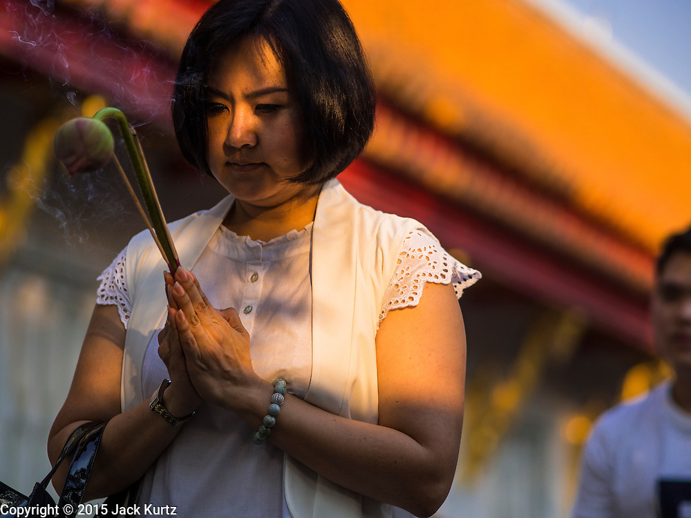 04 MARCH 2015 - BANGKOK, THAILAND: A woman carries flowers and incense while she prays and walks around the prayer hall at Wat Benchamabophit on Makha Bucha Day. Makha Bucha Day is an important Buddhist holy day and public holiday in Thailand, Cambodia, Laos, and Myanmar. Many people go to temples to perform merit-making activities on Makha Bucha Day. Wat Benchamabophit is one of the most popular Buddhist temples in Bangkok.      PHOTO BY JACK KURTZ