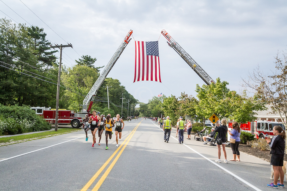 lead pack of men pass under fireman's American flag at mile 3