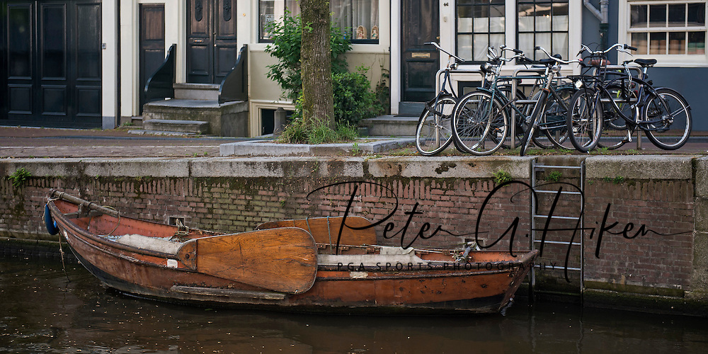 A small row boat and bicycles rest along side one of the canals in Amsterdam.