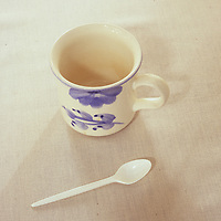 White mug with blue flower motif standing on white linen tablecloth next to white plastic teaspoon