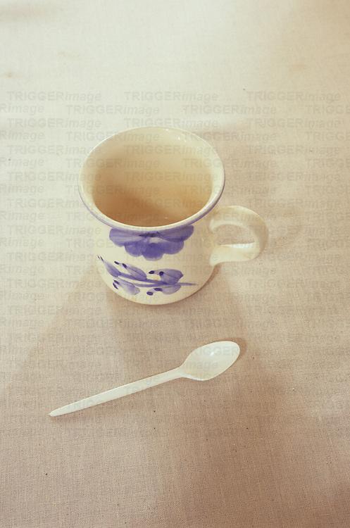 White mug with blue flower motif standing on white linen tablecloth next to white plastic teaspoon