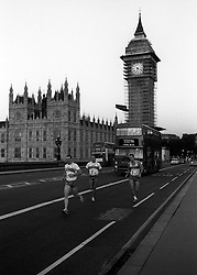 Striding out across Westminster Bridge, London, on the first stage of the 1985 London to Paris International Team Triathlon three-day endurance test are members of Team West One, who all live in Devon. (L-R) Richard Hudson, twice winner of the London Triathlon, Glen Cook and Paul Brew.  Fourth team member, Robin Brew, Olympic swimmer, Commonwealth Games silver medallist and the current UK and International Superstars  Champion, is not in the picture. Ten teams are entered to run, swim and cycle to the centre of Paris.