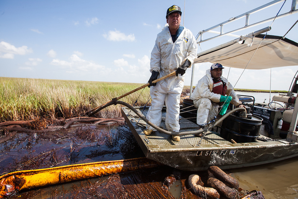Clean up crews work to vacuum up oil on the surface of Barataria Bay washed into the marshland in Plaquimenes Parish, Louisiana