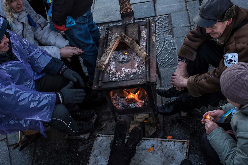 KIEV, UKRAINE - DECEMBER 6: Anti-government protesters warm themselves by a fire on Independence Square on December 6, 2013 in Kiev, Ukraine. Thousands of people have been protesting against the government since a decision by Ukrainian president Viktor Yanukovych to suspend a trade and partnership agreement with the European Union in favor of incentives from Russia. (Photo by Brendan Hoffman/Getty Images) *** Local Caption ***