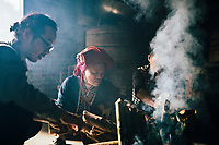 Cooking rice in bamboo on an open flame in Ta Phin, Vietnam.