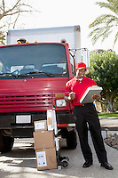 Young delivery man looking at delivery list on clipboard with truck in background